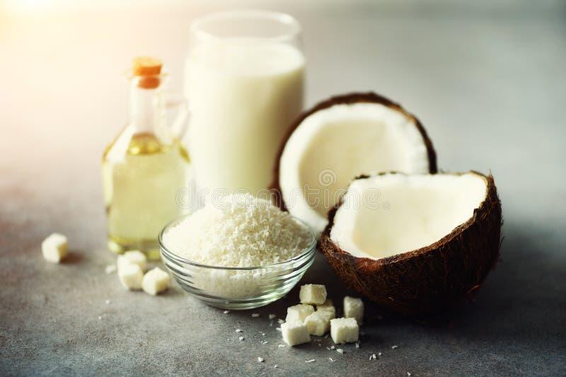 Productos de los cocos - leche, aceite, virutas en fondo concreto gris Copie el espacio Tratamiento del pelo, de la piel y del cu fotos de archivo libres de regalías