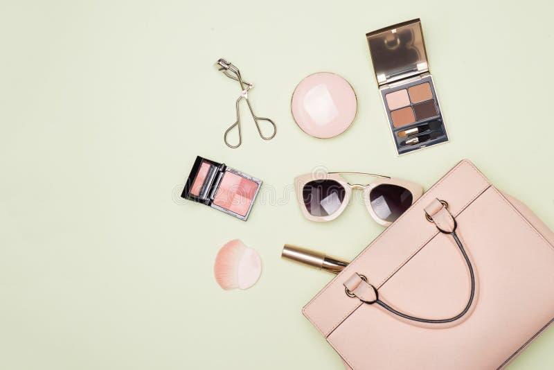 Productos de maquillaje con el bolso cosmético en fondo del color fotografía de archivo libre de regalías