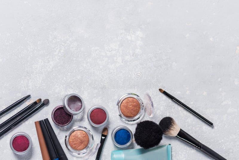 Productos de maquillaje con el cosmético, cepillos, lápices, sombra de ojos, crema de la mano, con el borde de la foto abajo, fon imagenes de archivo