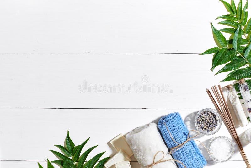 Productos del balneario Sales de baño, flores secas lavanda, jabón, velas y toalla Endecha plana en el fondo de madera blanco, vi fotos de archivo