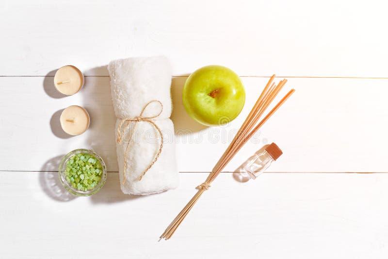 Productos del balneario Sales de baño, jabón, velas y toalla Endecha plana en el fondo de madera blanco, visión superior Llamarad foto de archivo