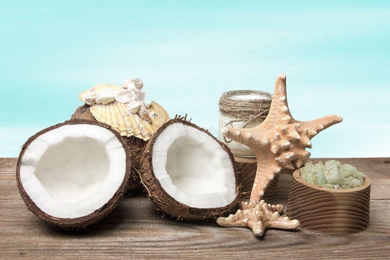 Productos del coco del balneario y accesorios marinos en los tableros de madera, en fondo de la turquesa fotografía de archivo