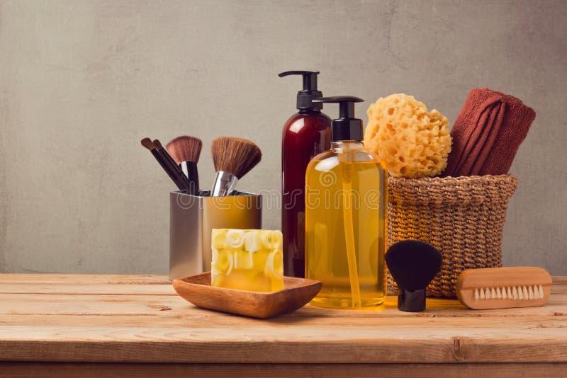 Productos del cuidado del cuerpo en la tabla de madera sobre fondo gris imagen de archivo libre de regalías