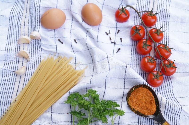 Productos para cocinar las pastas Tomate, huevo, espagueti, ajo, perejil, especias fotografía de archivo