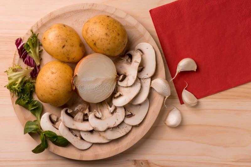 Productos para cocinar, setas, patatas, cebollas, ajo, hierbas imagen de archivo libre de regalías