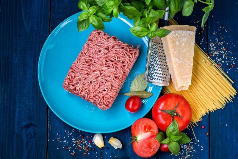 Productos para la preparación de las pastas boloñés Carne picadita, tomates, espaguetis, albahaca, queso parmesano, especias imágenes de archivo libres de regalías