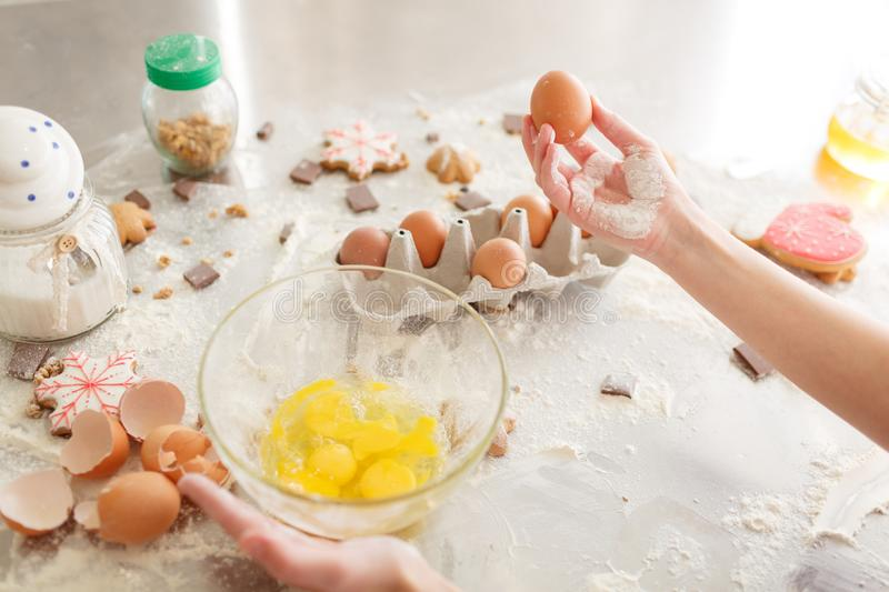 Products for baking. Kid& x27;s hands cook sweets. Flour with dough, eggs, eggshells, and biscuits on the kitchen table. royalty free stock images