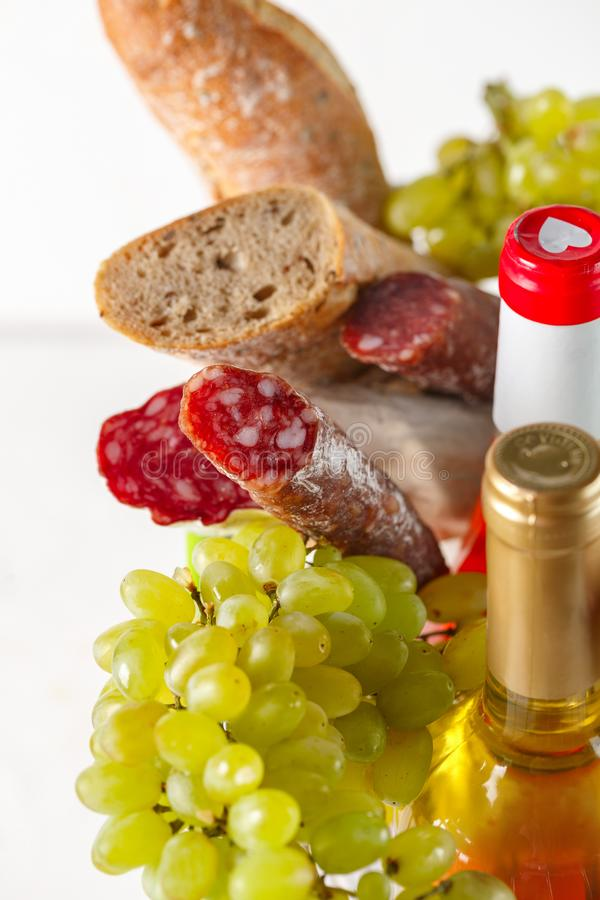 Shopping cart with groceries. Salami, grapes, bread, cheese and wine. Products in the basket. Salami, grapes, bread, cheese and wine closeup on white background stock image