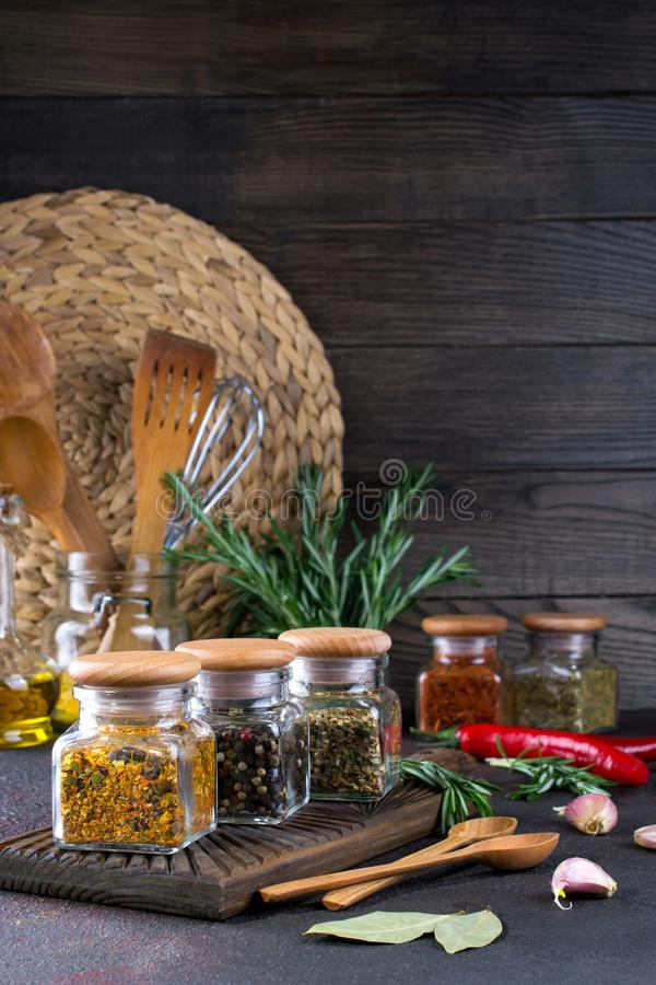 Products for cooking in kitchen, kitchen utensils, herbs, colorful dry spices in glass jars on dark stock photography
