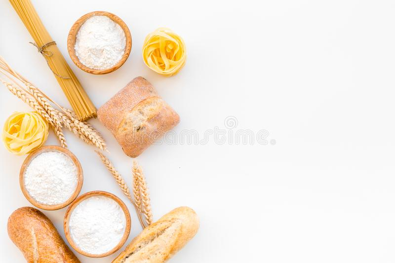 Products made of wheat flour. White flour in bowl, wheat ears, fresh bread and raw pasta on white background top view stock photos