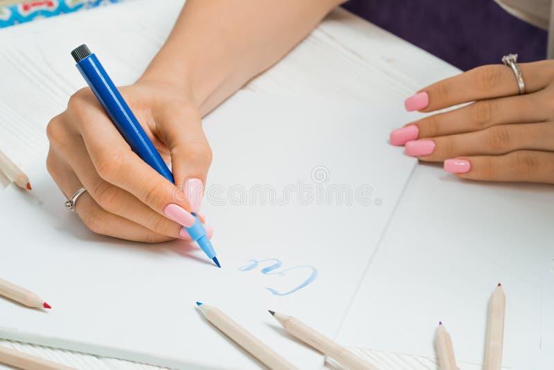 produisez La main femelle écrit de belles lettres bleues sur la toile dans le cadre coloré de stylos Manuscrit de calligraphie Ar photo libre de droits