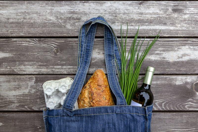 Produit frais dans le sac bleu du march? de denim sur le fond en bois, configuration plate Sac ? provisions r?utilisable ?cologiq image stock