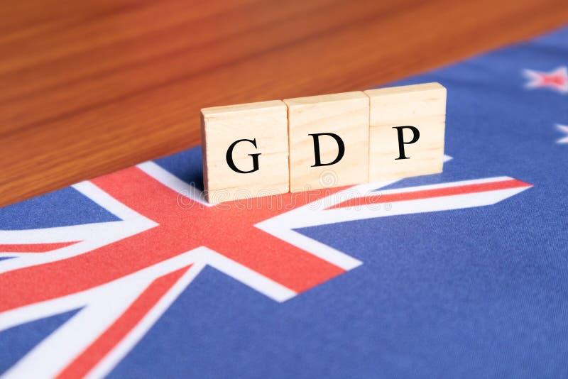 Produit intérieur brut ou PIB de l'Australie dans les caractères gras en bois sur le drapeau australien photographie stock