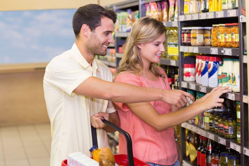 Download Produits Alimentaires De Achat De Sourire De Couples Lumineux Montrant L'étagère Photo stock - Image du épicerie, achats: 56487550