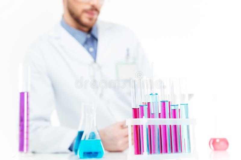 Produits chimiques pleuvants à torrents de scientifique dans un laboratoire photographie stock libre de droits