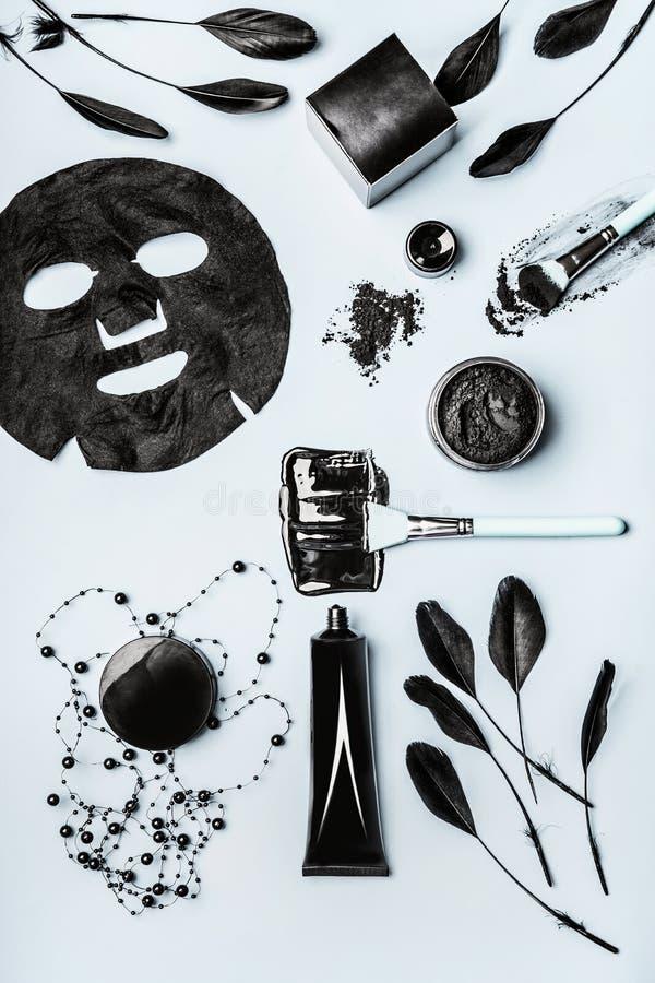 Produits cosmétiques faciaux de beauté avec du charbon actif : poudre, masque principal noir, masque de feuille et accessoires d' image stock