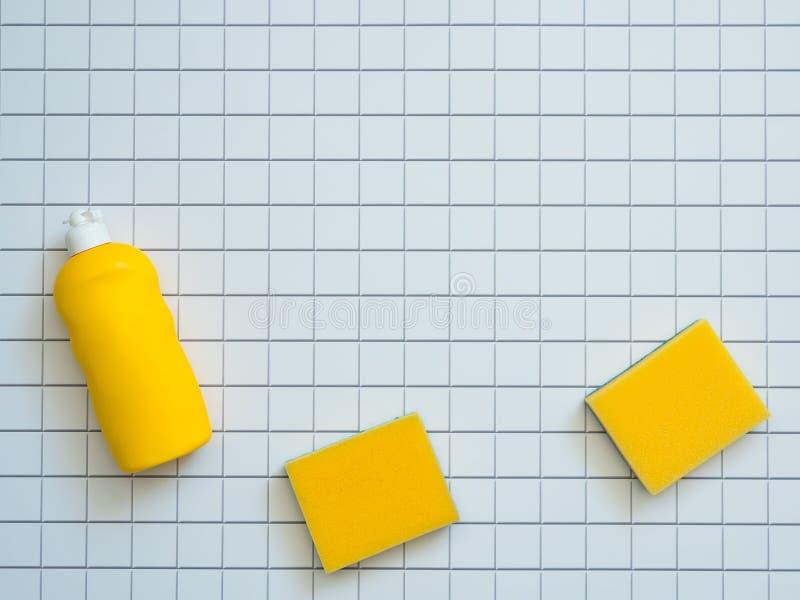 Produits d'entretien jaunes de maison sur le fond blanc de mosaïque avec l'espace de copie Concept d'hygiène et de propreté photo stock