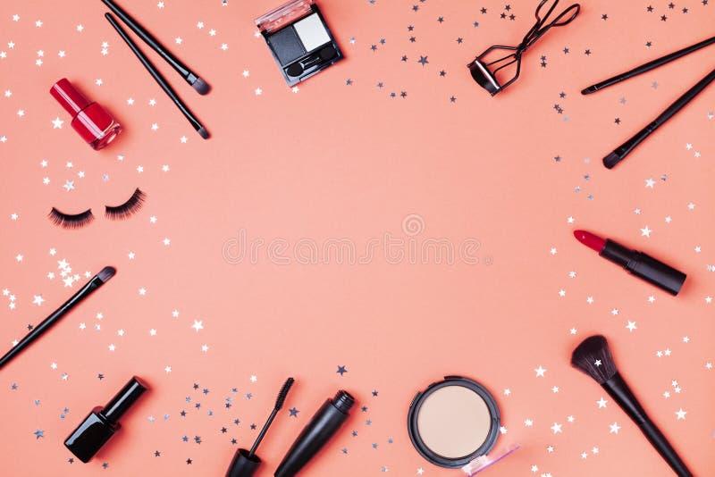 Produits de beauté et cosmétique pour les confettis d'étoile décorés par maquillage de femme sur la vue supérieure de corail de t photographie stock