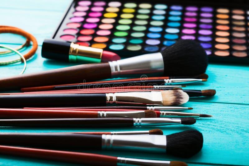 Produits de beauté pour le maquillage Ombres, brosses Cosmétiques sur le fond en bois bleu Vue supérieure Foyer sélectif Copiez l photo stock