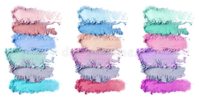 Produits de maquillage écrasés sur le fond blanc Ensemble de couleur de fards à paupières image stock
