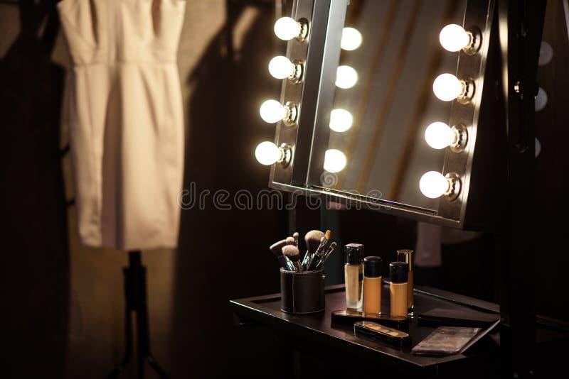 Produits de maquillage et robe à l'arrière plan images stock