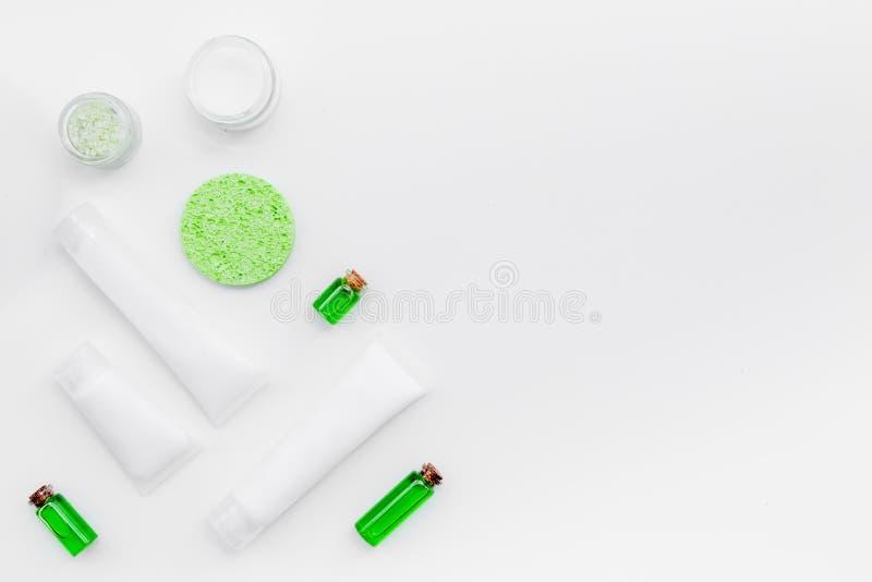 Produits de soin pour la peau organiques Crème, lotion, tonique huilez près des feuilles vertes sur le modèle blanc de vue supéri photos stock