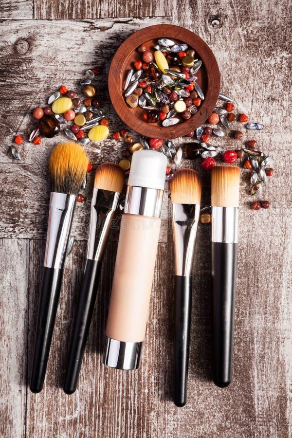 Produits et brosses de cosmétiques dans l'image conceptuelle au-dessus du fond en bois photos libres de droits