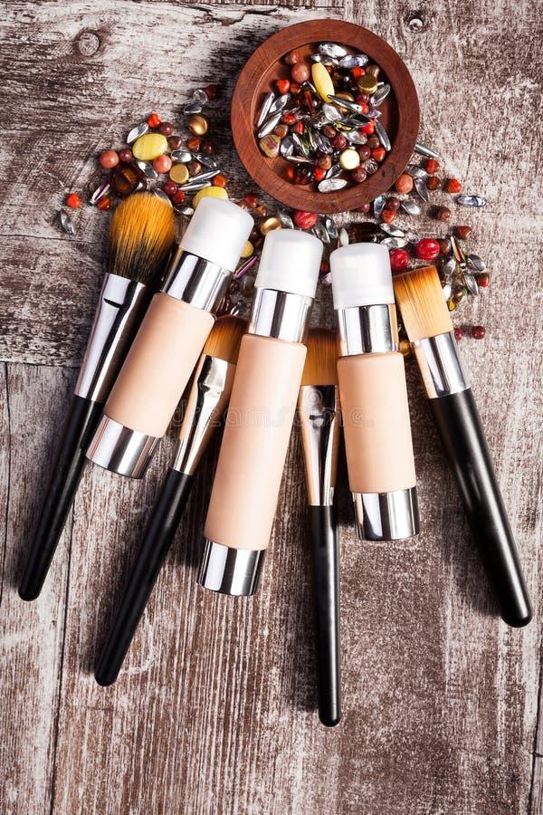 Produits et brosses de cosmétiques dans l'image conceptuelle au-dessus du fond en bois photo stock