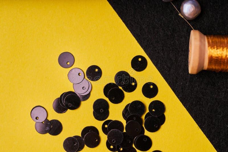 Produits et outils de broderie Bobine avec le fil, les perles et les paillettes métalliques sur le feutre noir image stock