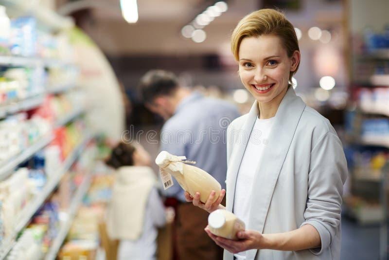 Produits laitiers de achat de sourire de femme photo libre de droits