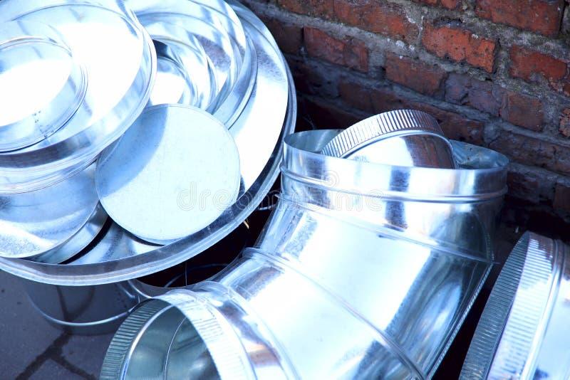 Produits métalliques de différentes formes pour des avances de l'eau et d'air dans la perspective d'un mur de briques photos stock