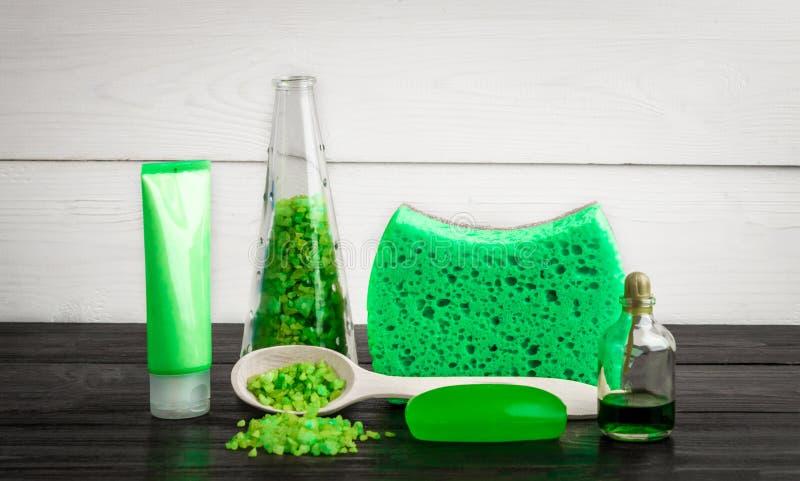 Produits verts de traitement de beauté de composition dans des couleurs vertes : shampooing, savon, sel de bain, huile photos libres de droits