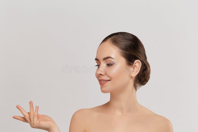 Produkt f?r kvinna?verraskningvisning Uttrycksfullt peka f?r h?rlig flicka till sidan Framlägga din annonsering Uttrycksfullt ans arkivbild
