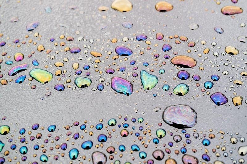 Produkt przerobu ropy naftowej dostać w wodę i na powierzchni wodnych kropelek tworzący wzory zdjęcia stock