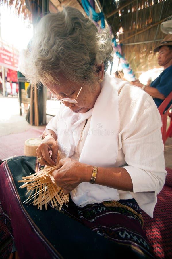 Produkt vid den gjorda handen -, handen av höga etniska kvinnahåll tog bambuband för att väva in i olikt royaltyfri foto