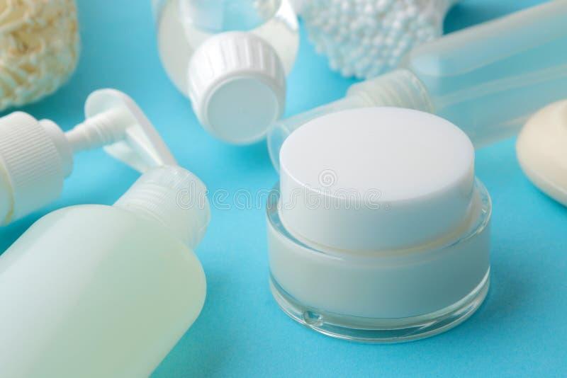Produkte der pers?nlichen Hygiene K?rperpflegekosmetik Weiße Flaschen und Phiolen auf einem blauen Hintergrund Badekurort relax lizenzfreies stockfoto