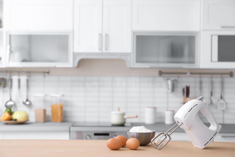 Produkte, Mischer und unscharfe Ansicht des Kücheninnenraums lizenzfreie stockfotos