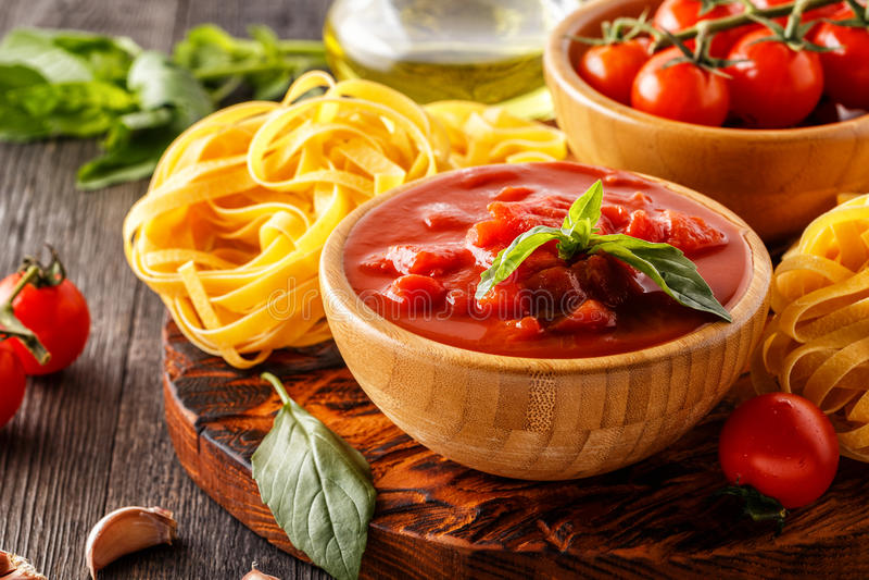 Produkter för att laga mat - tomatsås, pasta, tomater, vitlök arkivfoton