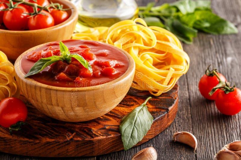 Produkter för att laga mat - tomatsås, pasta, tomater, vitlök royaltyfria foton