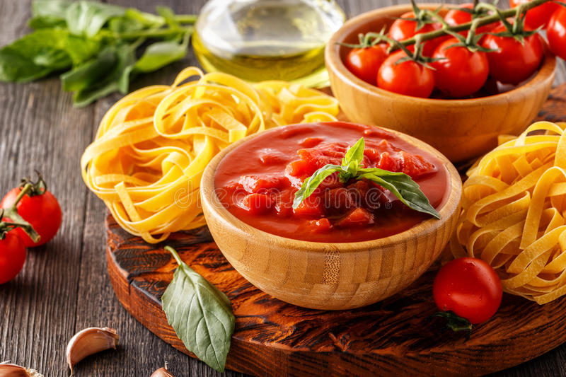 Produkter för att laga mat - tomatsås, pasta, tomater, vitlök, ol arkivbild