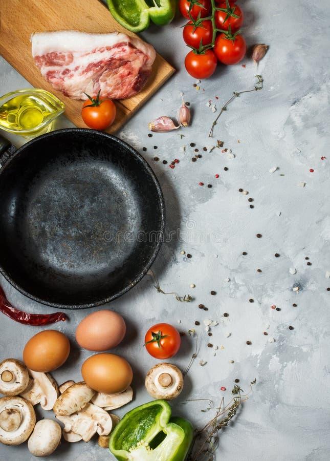 Produkter för frukost, ägg, bacon, grönsaker, örter på stenbakgrund, bästa sikt med kopieringsutrymme royaltyfria foton