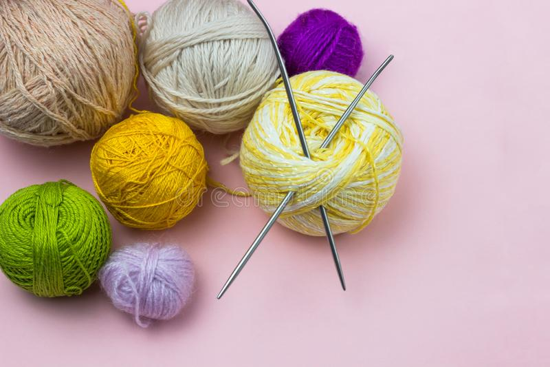 Produkter för handarbete som sticker Bollar av gult, grönt purpurfärgat garn, stickor på en rosa bakgrund arkivfoto