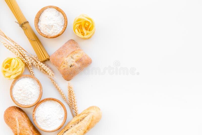 Produkter gjorde av vetemjöl Vitt mjöl i bunke, veteöron, nytt bröd och rå pasta på bästa sikt för vit bakgrund arkivfoton