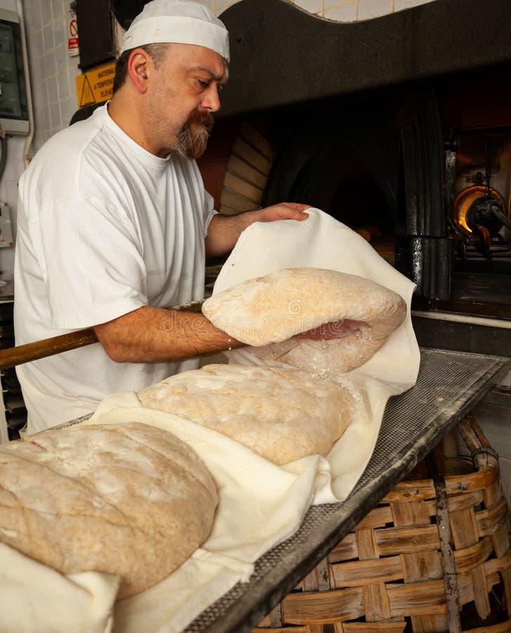 Produktion av bakat bröd med en träugn i ett bageri arkivbild