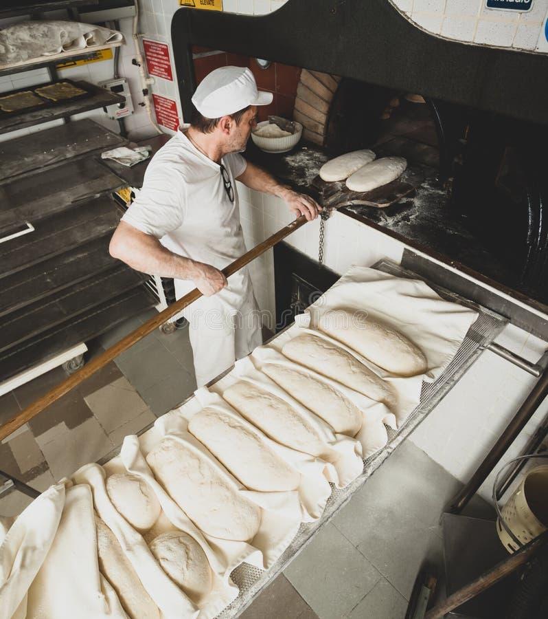 Produktion av bakat bröd med en träugn i ett bageri royaltyfri fotografi