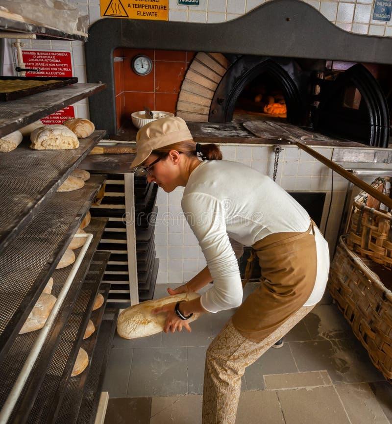 Produktion av bakat bröd med en träugn i ett bageri royaltyfria bilder