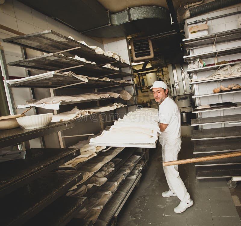 Produktion av bakat bröd med en träugn i ett bageri royaltyfri bild