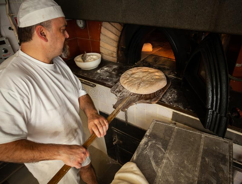 Produktion av bakat bröd med en träugn i ett bageri arkivbilder