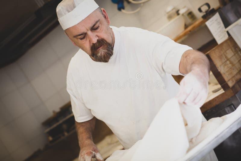 Produktion av bakat bröd med en träugn i ett bageri fotografering för bildbyråer