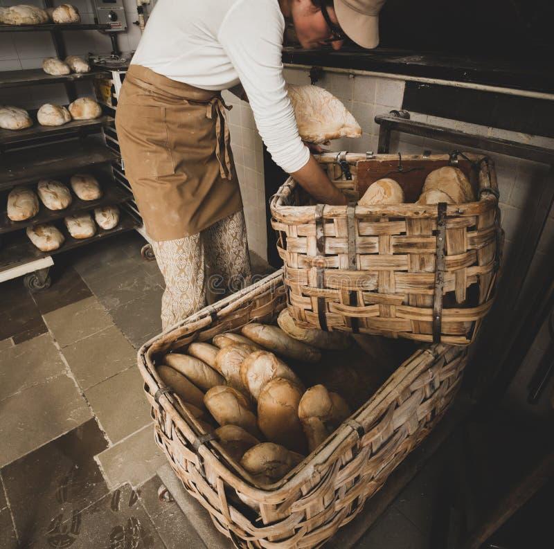 Produktion av bakat bröd med en träugn i ett bageri arkivfoton